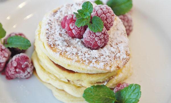 โปรตีนแพนเค้กตกแต่งราสเบอร์รี่และไอซิ่งบนจาน